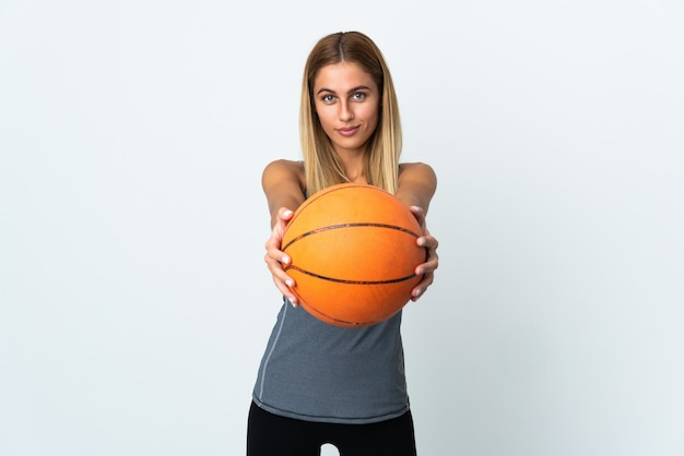 Young blonde woman over isolated background playing basketball