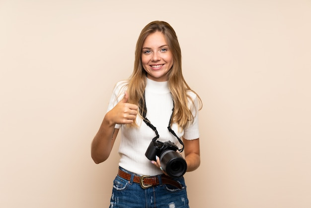 Young blonde woman over isolated background with a professional camera and with thumb up