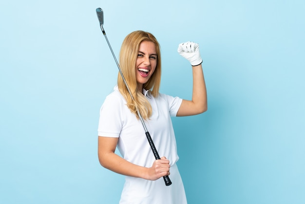 Young blonde woman over isolated blue playing golf and celebrating a victory