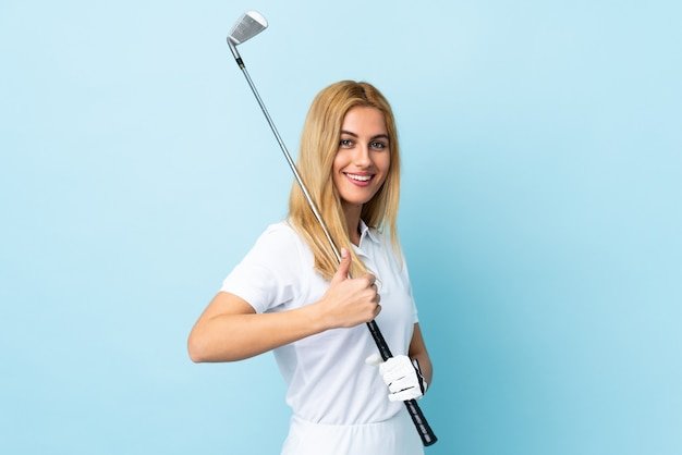 Young blonde woman over isolated blue playing golf and with thumbs up