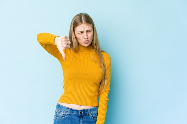Young blonde woman isolated on blue wall showing thumb down and expressing dislike.