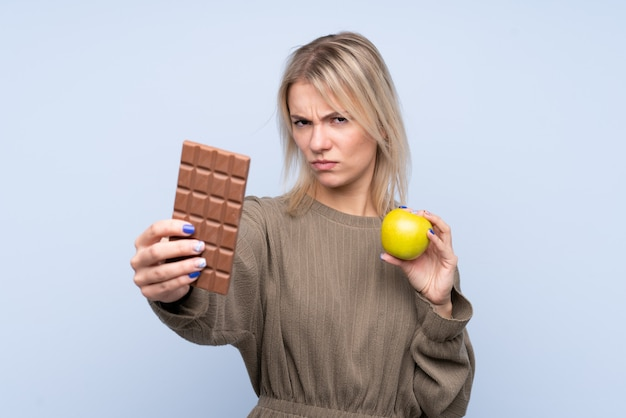 Young blonde woman over isolated blue wall taking a chocolate tablet in one hand and an apple in the other