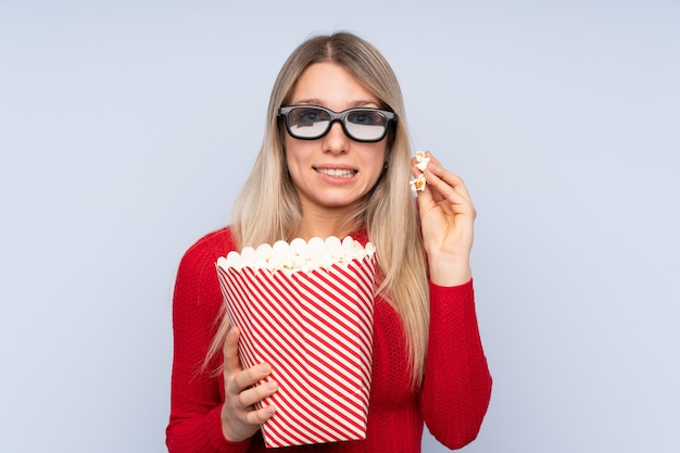 Young blonde woman over isolated blue wall with 3d glasses and holding a big bucket of popcorns