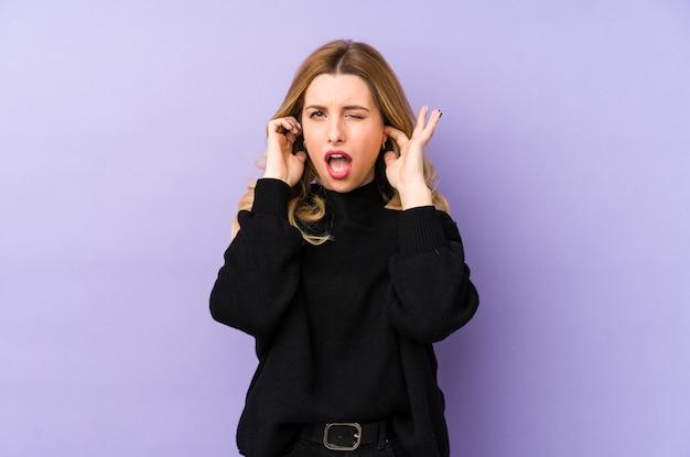 Молодая белокурая женщина изолировала уши заволакивания руками.