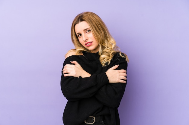 Young blonde woman isolated going cold due to low temperature or a sickness.