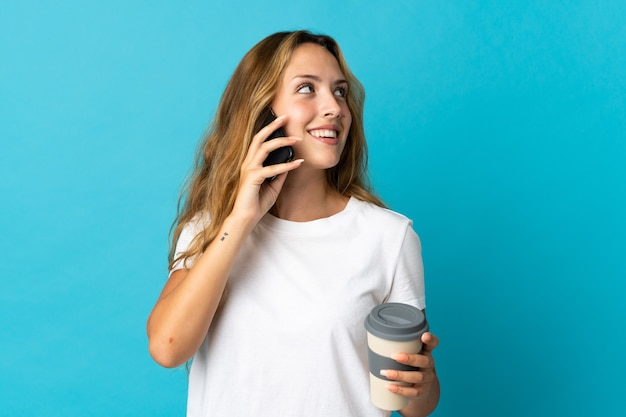 Молодая блондинка женщина изолирована на синем фоне держит кофе на вынос и мобильный