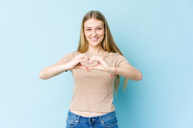 Молодая блондинка женщина, изолированных на синем фоне улыбается и показывает форму сердца руками.