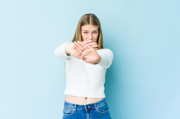 青の背景に孤立した若いブロンドの女性は、一時停止の標識を示している手を伸ばして立って、あなたを妨げています。