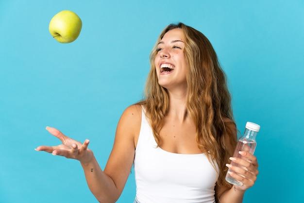 Молодая блондинка женщина изолирована на синем фоне с яблоком и бутылкой воды