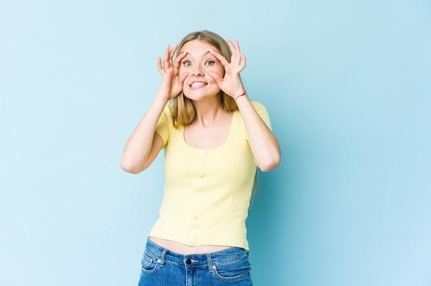 Молодая блондинка женщина изолирована на синем, держа глаза открытыми, чтобы найти возможность успеха.