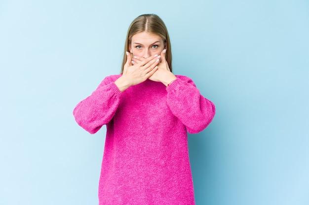 否定ジェスチャーをしている青い壁に孤立した若いブロンドの女性