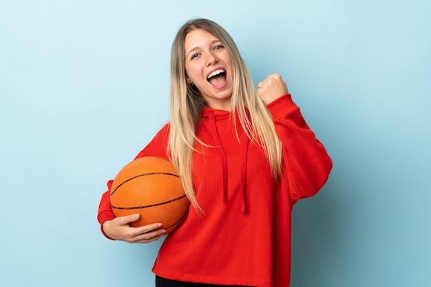 파란색 벽 농구에 고립 된 젊은 금발의 여자