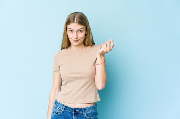 Молодая блондинка изолирована на синей стене, показывая, что у нее нет денег