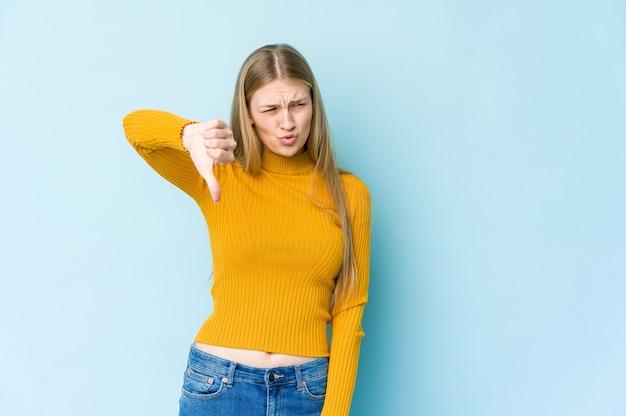 親指を下に示し、嫌悪感を表現する青い壁に孤立した若いブロンドの女性。