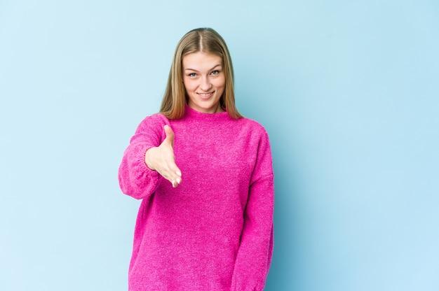 Молодая блондинка женщина изолирована на синей стене, протягивая руку вперед в приветствии жестом