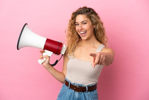Молодая блондинка женщина изолирована на розовом фоне держит мегафон и улыбается, указывая на фронт