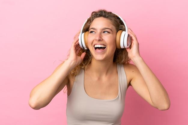 Молодая блондинка женщина изолирована на розовом фоне прослушивания музыки и пения