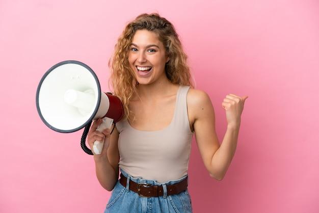 Молодая блондинка женщина изолирована на розовом фоне кричит через мегафон и указывает сторону