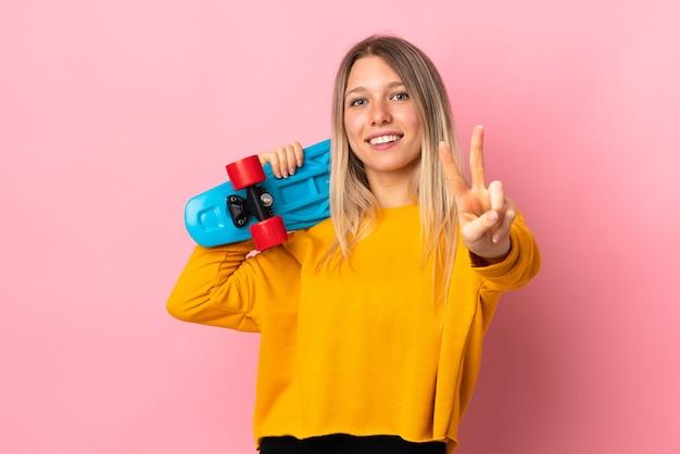 Молодая блондинка изолирована на розовой стене с коньком, делая жест победы