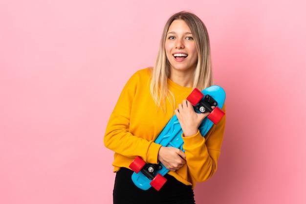 Молодая блондинка изолирована на розовой стене с коньком со счастливым выражением лица