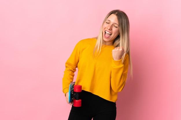 Молодая блондинка изолирована на розовой стене с коньком