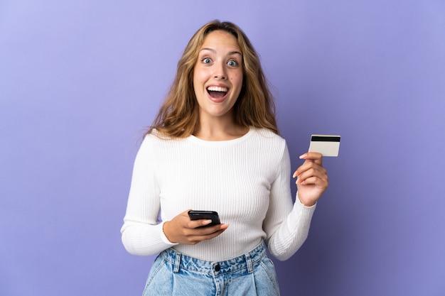 Молодая блондинка женщина изолирована на фиолетовом фоне, покупая с мобильного и держа кредитную карту с удивленным выражением лица
