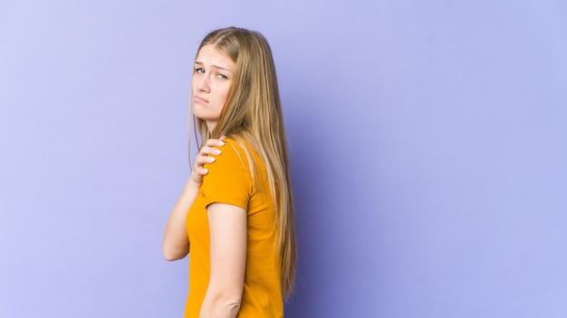 어깨 통증 데 보라색 배경에 고립 된 젊은 금발의 여자.
