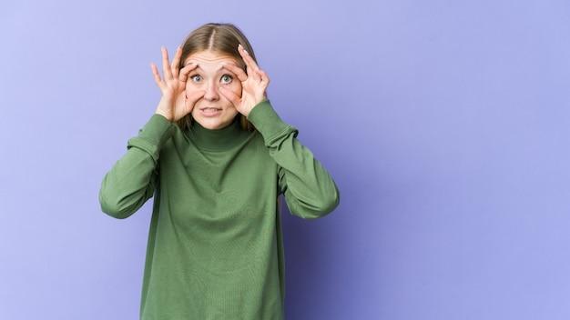 Молодая блондинка женщина изолирована на фиолетовом, держа глаза открытыми, чтобы найти возможность успеха.