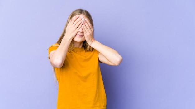 Молодая блондинка, изолированная на фиолетовой стене, боится закрывать глаза руками