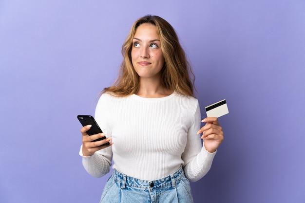 考えながらクレジットカードで携帯電話で購入する紫色の壁に孤立した若いブロンドの女性