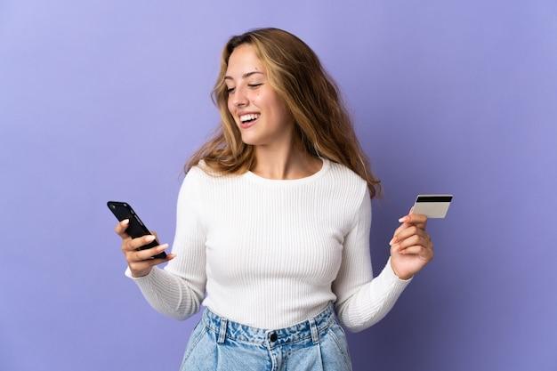 Молодая блондинка женщина изолирована на фиолетовой стене, покупая с мобильного телефона с помощью кредитной карты
