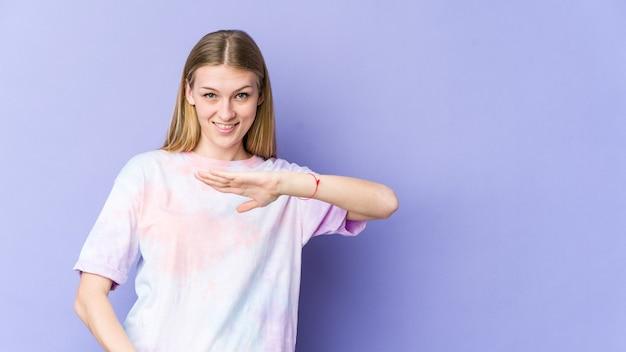 Молодая блондинка женщина изолирована на фиолетовой стене, держа что-то обеими руками, презентация продукта