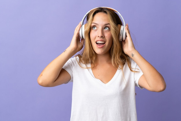 Молодая блондинка изолирована на фиолетовой стене в пижаме и держит подушку и слушает музыку