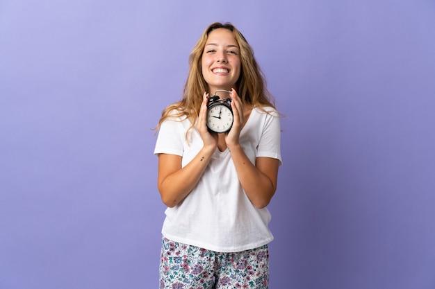 Молодая блондинка изолирована на фиолетовой стене в пижаме и держит часы со счастливым выражением лица