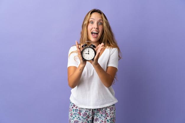 Молодая блондинка изолирована на фиолетовой стене в пижаме и держит часы с удивленным выражением лица