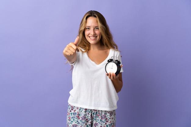 Молодая блондинка изолирована на фиолетовой стене в пижаме и держит часы с большим пальцем вверх