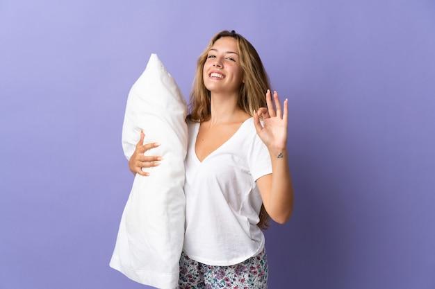 Молодая блондинка изолирована на фиолетовой стене в пижаме и показывает пальцами знак ок
