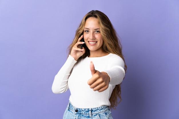 Молодая блондинка изолирована на фиолетовой стене, разговаривает с мобильным телефоном и показывает палец вверх