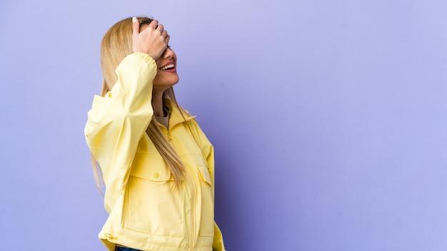 Молодая блондинка женщина, изолированных на фиолетовой стене смеется радостно, держа руки на голове. концепция счастья.