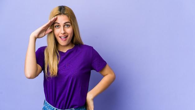 Молодая блондинка, изолированная на фиолетовой стене, громко кричит, держит глаза открытыми, а руки напряженными.