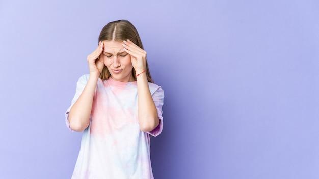 こめかみに触れて頭痛を持っている紫色の壁に孤立した若いブロンドの女性