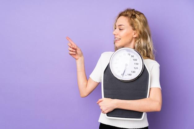 Молодая белокурая женщина изолированная на фиолетовой стене с весами и указывая стороной