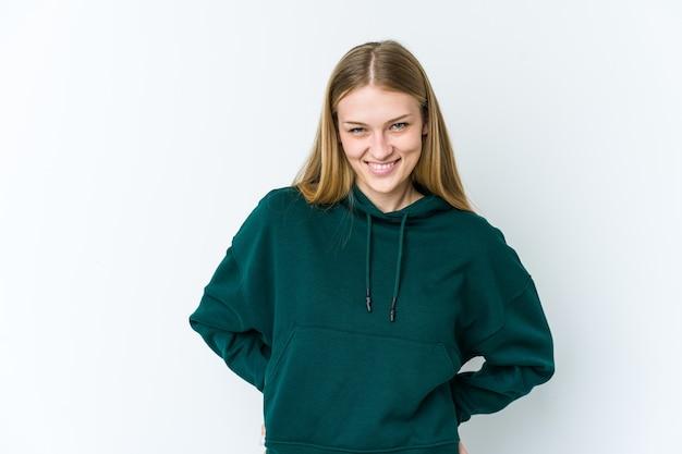 幸せな、笑顔で陽気な白い壁に隔離の若いブロンドの女性