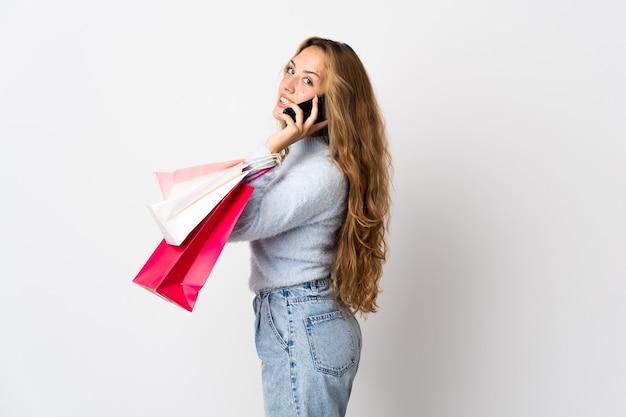 흰 벽에 쇼핑백을 들고 그녀의 휴대 전화로 친구를 호출하는 젊은 금발의 여자