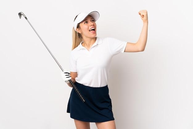 골프를 재생하고 승리를 축하 흰 벽에 고립 된 젊은 금발의 여자