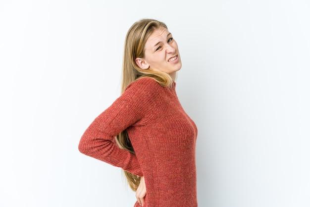 背中の痛みに苦しんで白い壁に孤立した若いブロンドの女性
