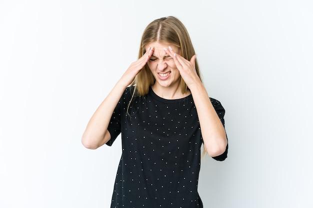 こめかみに触れて頭痛を持っている白い壁に孤立した若いブロンドの女性