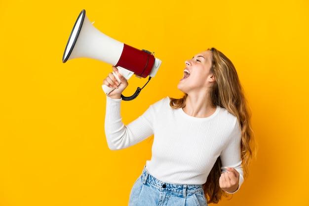 Молодая блондинка изолирована на желтом фоне, кричит в мегафон, чтобы объявить что-то в боковом положении