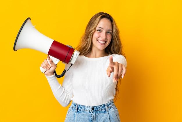 Молодая блондинка женщина изолирована на желтом, держа мегафон и улыбаясь, указывая на фронт