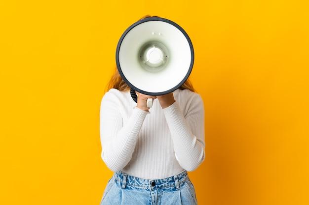 何かを発表するためにメガホンを通して叫んでいる黄色の壁に孤立した若いブロンドの女性